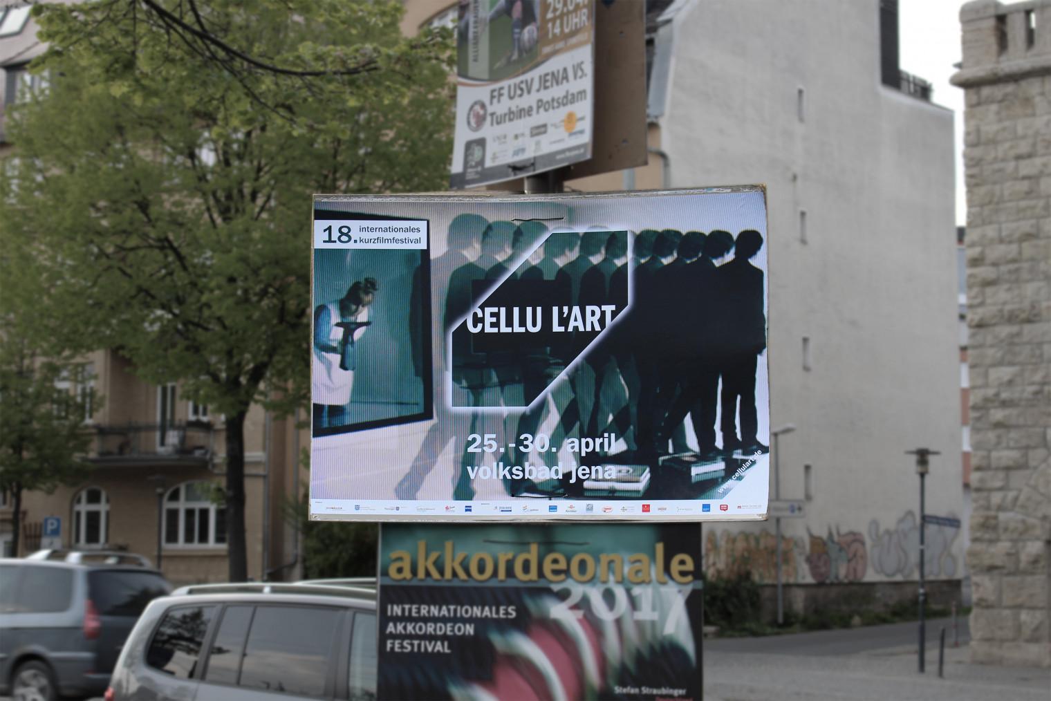 Ein Laternenpfahl mit verschiedenen Veranstaltungsplakaten an einer Straße. In der Mitte hängt ein Plakat des cellu l'art Festivals.