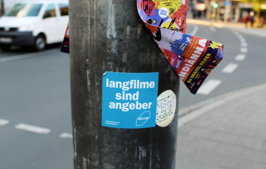 Laternenpfahl an einer Straße mit vielen Aufklebern. In der Mitte klebt ein blauer Sticker des cellu l'art mit dem Spruch