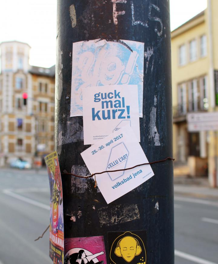 Laternenpfahl an einer Straße mit vielen Aufklebern. In der Mitte kleben zwei ein weiße Sticker des cellu l'art. Einer mit dem Spruch