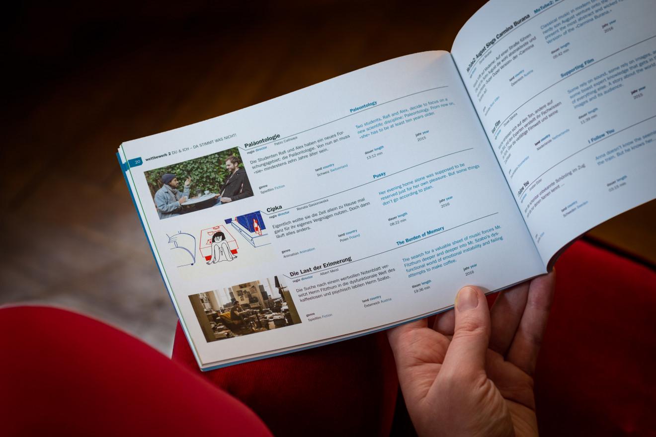 Eine Seite aus dem Festivalkatalog von oben. Das zweisprachige Layout des Festivalprogramms ist erkennbar.