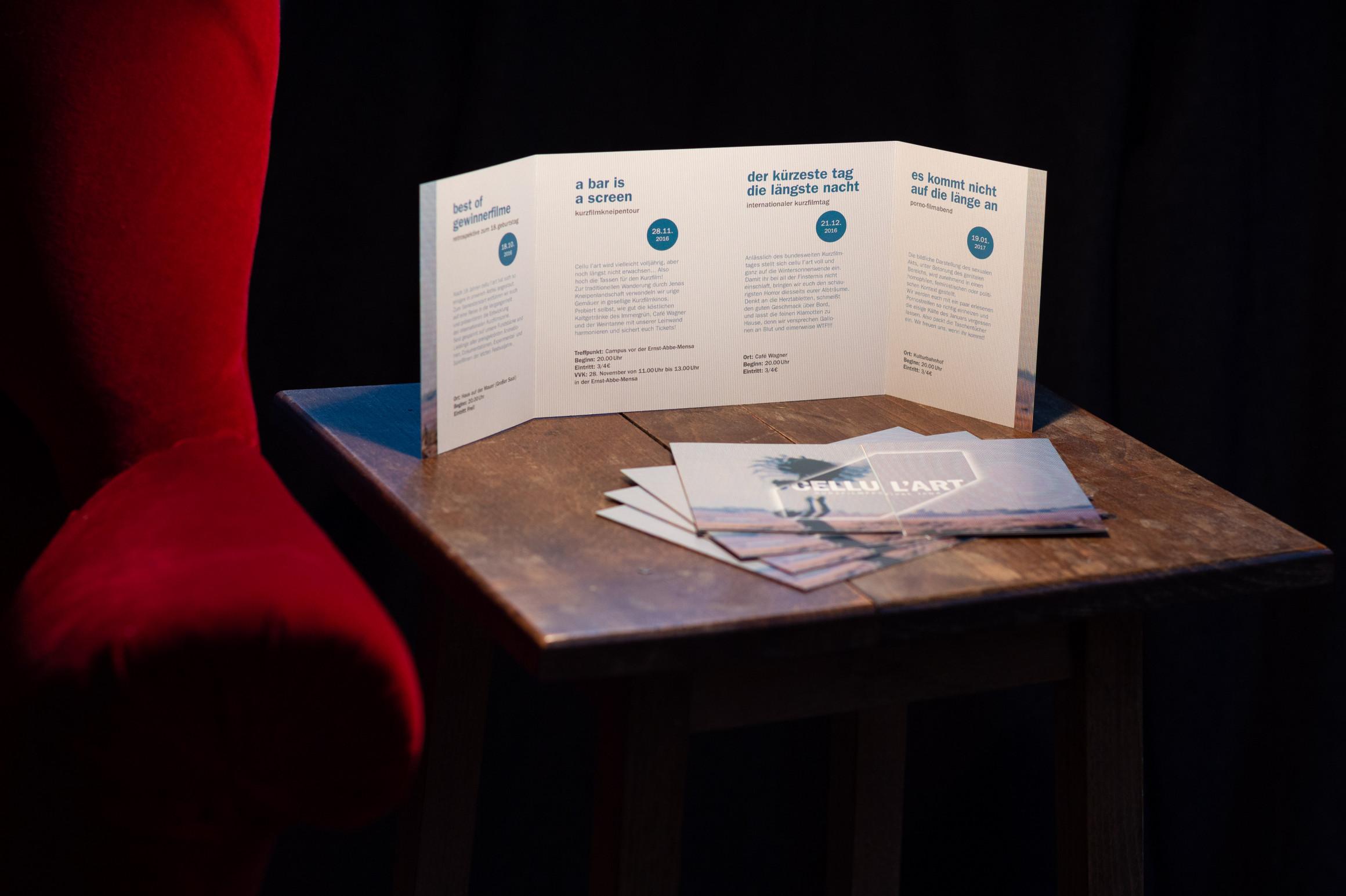 Ein Leporello mit Altarfalz bzw. ein Programm-Flyer steht auf einem kleinen Holztische neben einem roten Samtsessel.