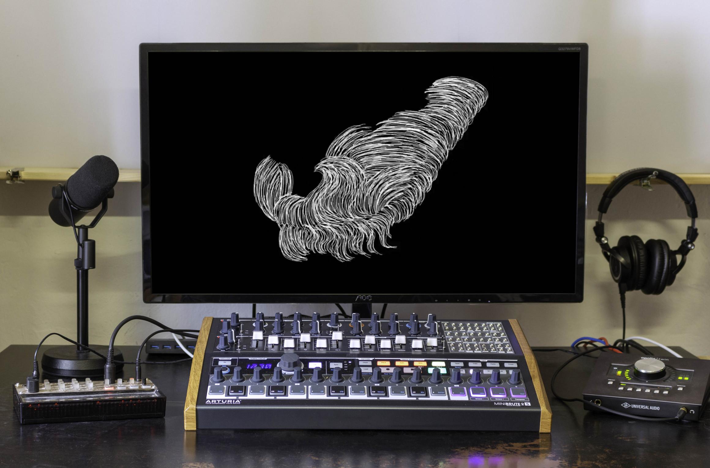 Schreibtisch mit Bildschirm, Kopfhörern, Mikrofon und Mischpult. Auf dem Bildschirm ist ein Standbild des Musikvideos zu sehen: eine abstrakte weiße Form auf schwarzem Hintergrund.