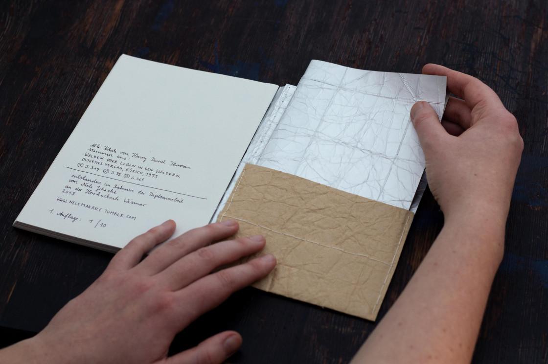 Aus der Umschlagtasche hinten im Buch wird das Heft mit der theoretischen Arbeit gezogen.