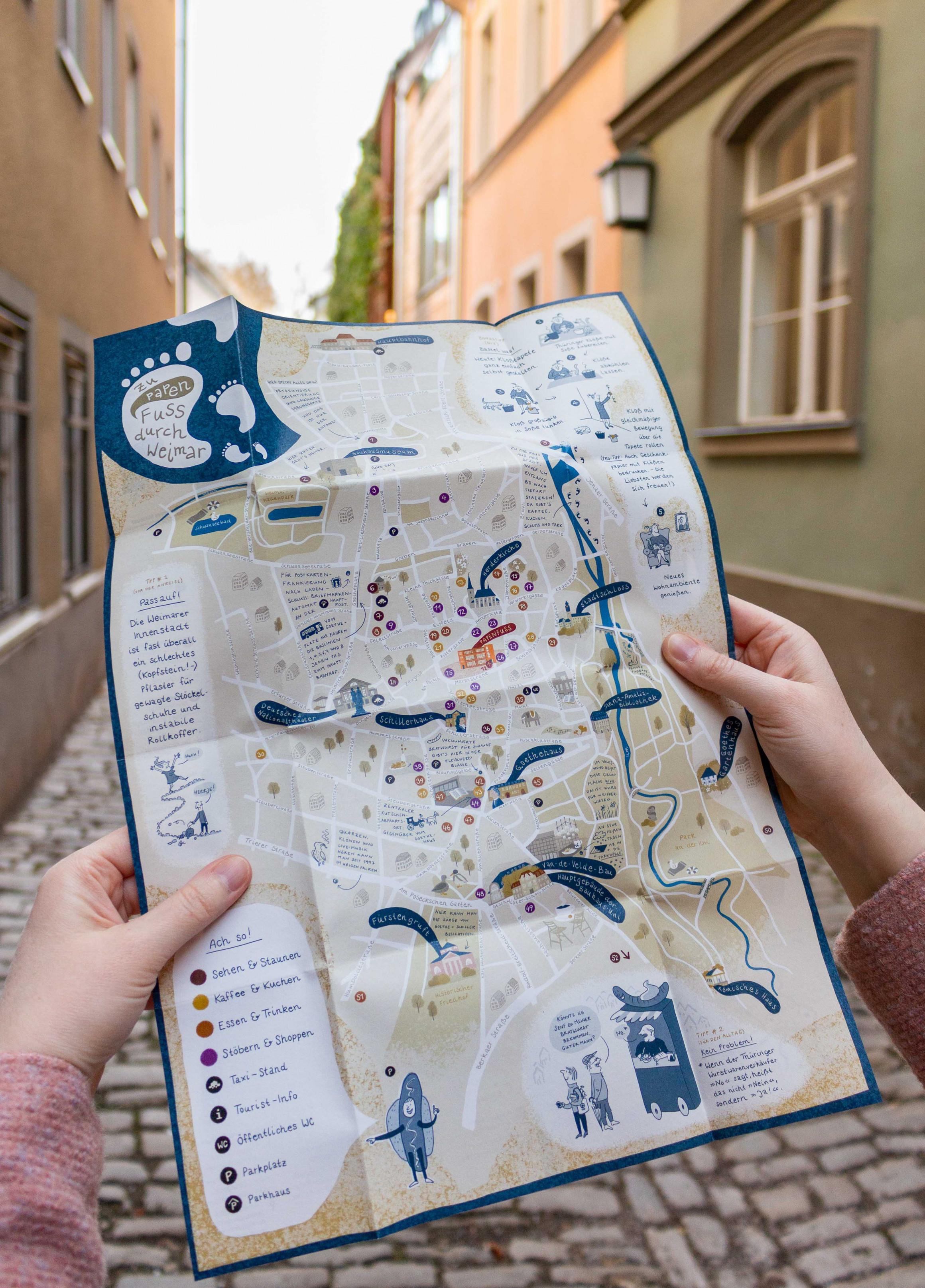 Aufgeklappter Stadtplan vor einer Stadtkulisse.