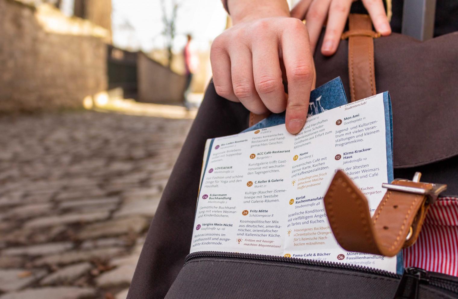 Eine Hand holt den Stadtplan aus der Außentasche eines Rucksacks. Im Hintergrund sieht man eine sonnige Straße.