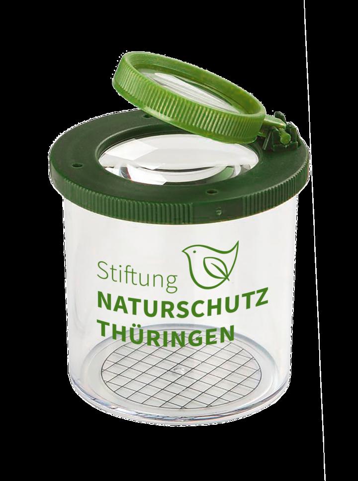 Eine Becherlupe mit grünem Deckel und dem Logo der Stiftung Naturschutz Thüringen.