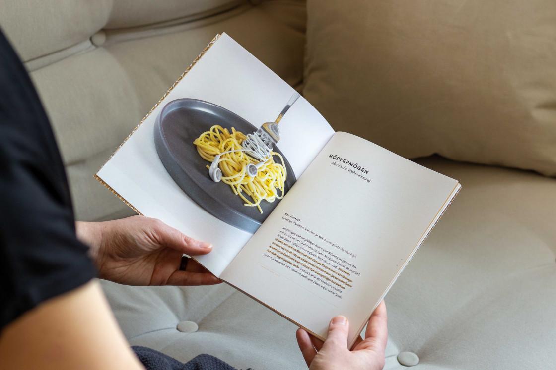 Das aufgeschlagene Heft Ohrenschmaus wird in Händen gehalten. Das Foto im Heft zeigt einen Teller Spaghettis. Darin steckt eine Gabel mit am Kabel aufgedrehten Kopfhörern.