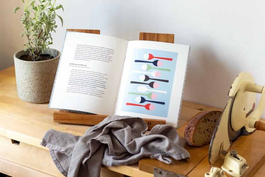 Ein aufgeschlagenes Heft steht in einem Buchständer. Links davon ein Salbeistrauch im Topf, rechts davon eine handbetrieben Brotschneidemaschine.