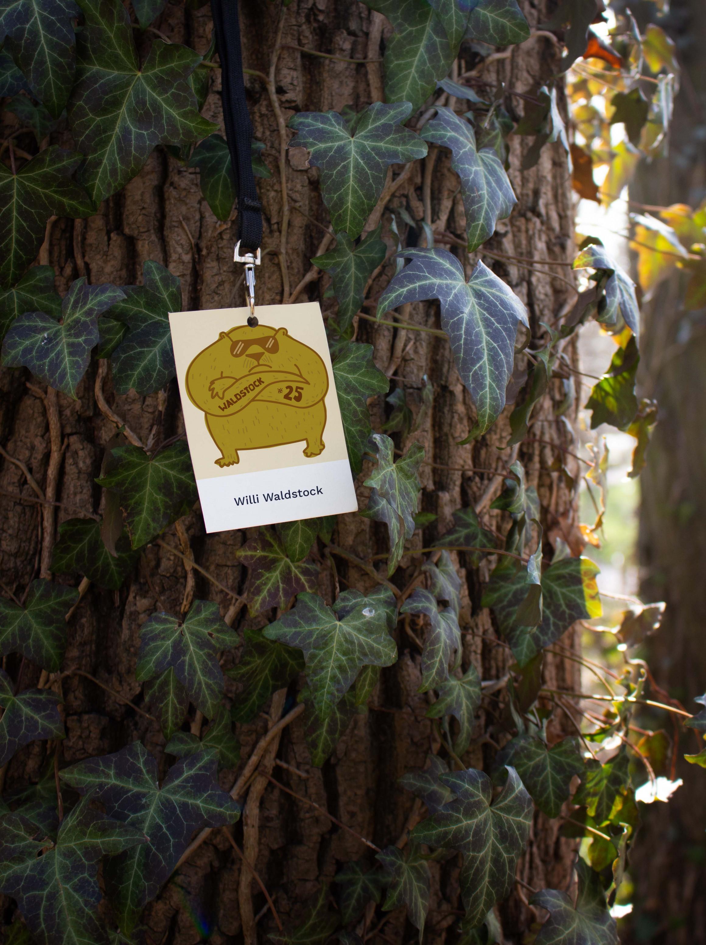 Backstage-Pass hängt an einem Baumstamm, der mit Efeu bewachsen ist. Auf dem Pass ist die Zeichnung eines dicken Bären, der das Waldstock-Logo auf den Unterarm tätowiert hat.