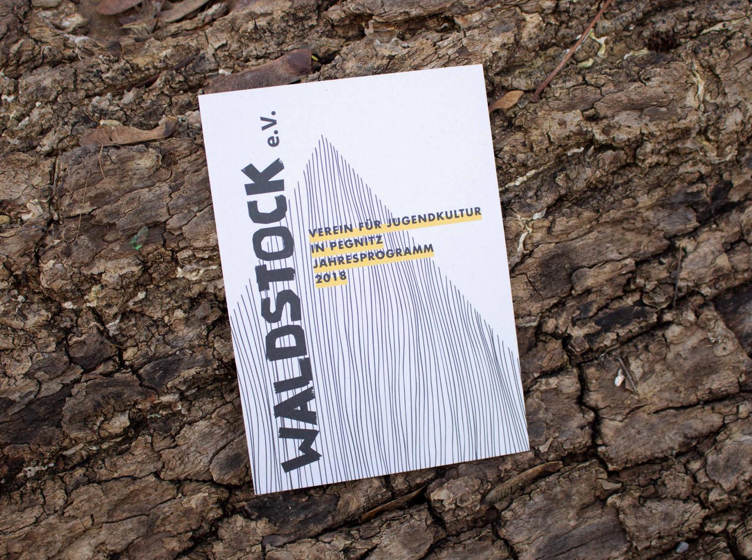 Das Jahresprogramm des Waldstock-Vereins liegt auf einem Baumstamm.
