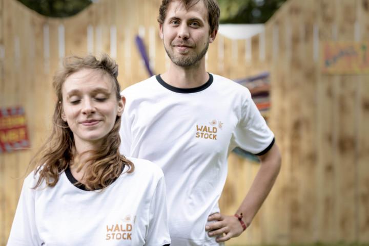 Eine junge Frau und ein junger Mann tragen Waldstock-Shirts.