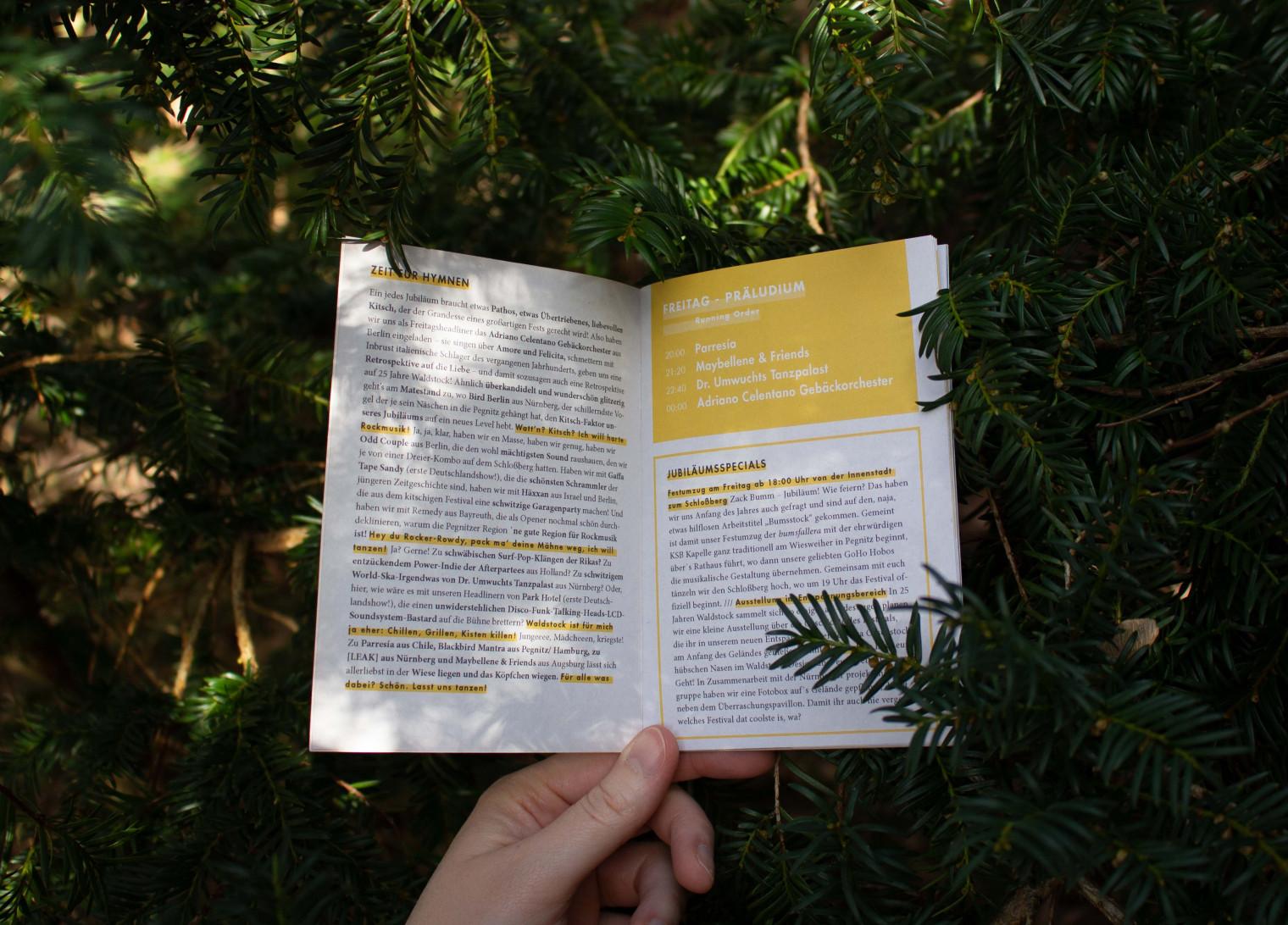 Aufgeschlagenes Programmheft, im Hintergrund Nadelbaum.